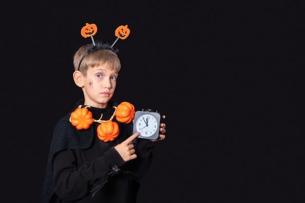 Mode de vie d'halloween. garçon avec une araignée sur sa joue et une citrouille perles tenant un réveil noir sur fond noir. il est temps de célébrer halloween. concept d'halloween heureux