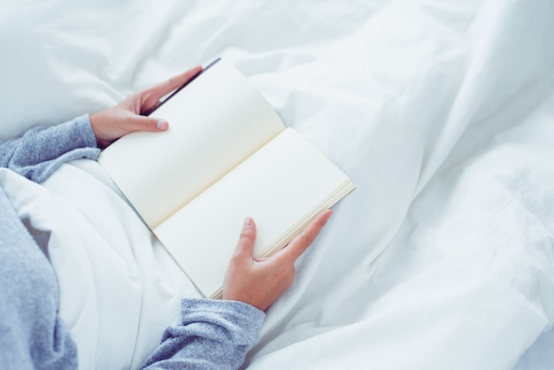Mode de vie heureux jeune femme asiatique profitant de s'allonger sur le lit en lisant un livre plaisir en vêtements de loisirs