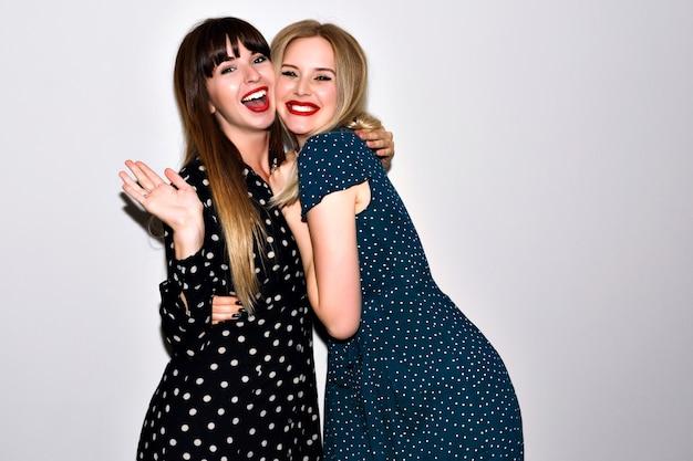 Mode de vie intérieur portrait lumineux de deux jolies meilleures amies, câlins et montrant v science, élégantes robes féminines et maquillage lumineux, style hipster, montrant v science.