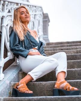 Mode de vie, jeune blonde caucasienne assise dans les escaliers avec un t-shirt blanc et une veste