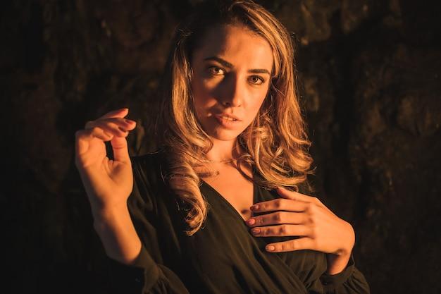 Mode de vie une jeune blonde de race blanche dans une robe noire à l'intérieur d'une grotte éclairée par une lumière jaune portrait de la jeune femme profitant de l'après-midi d'automne