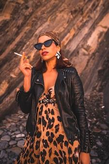 Mode de vie, une jeune brune dans une veste en cuir et une robe léopard sur un coucher de soleil sur la côte portant des lunettes de soleil. regard de jeune fille fumant avec un foulard et des lunettes triangulaires