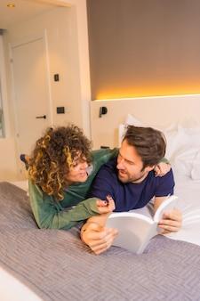 Mode de vie, un jeune couple de race blanche, en pyjama au lit en lisant un joli livre embrassé