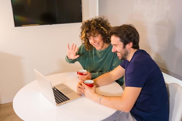 Mode de vie, un jeune couple de race blanche en pyjama prenant son petit déjeuner dans la cuisine, faisant un appel vidéo familial sur l'ordinateur, une nouvelle norme