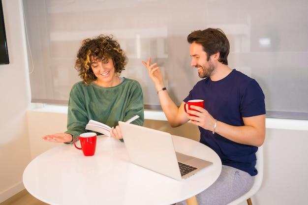Mode de vie, un jeune couple de race blanche en pyjama prenant son petit déjeuner dans la cuisine, faisant un appel vidéo familial sur l'ordinateur