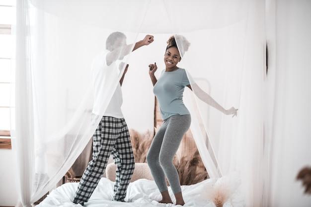 Mode de vie. jeune homme et femme à la peau foncée heureux en pyjama dansant sur le lit le matin de bonne humeur