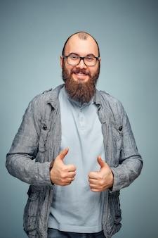 Mode de vie d'un jeune homme réussi avec des lunettes, une barbe, une veste en jean à la mode montrant les pouces vers le haut