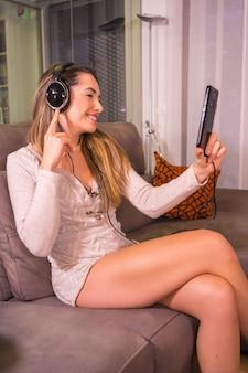 Mode de vie à la maison, jeune femme de race blanche à l'écoute d'une playlist de musique avec des écouteurs sur le canapé à la maison