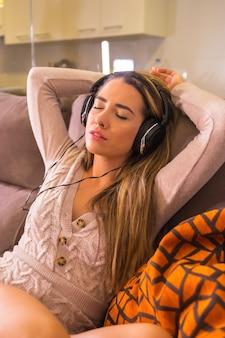 Mode de vie à la maison, jeune femme de race blanche, écouter de la musique avec des écouteurs sur le canapé à la maison