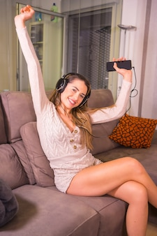 Mode de vie à la maison, portrait d'une blonde caucasienne souriante et dansant sur une liste de lecture avec des écouteurs sur le canapé à la maison