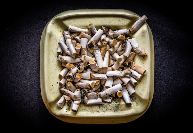 Mode de vie malsain - cendrier plein de souche de cigarettes sur fond sombre