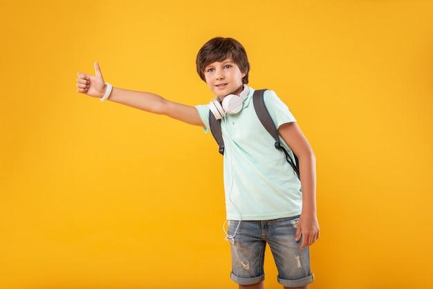 Mode de vie moderne. joyeux beau garçon portant un cartable et tenant son pouce vers le haut