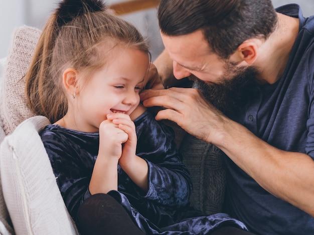 Mode de vie parental heureux. père attentionné complétant sa jolie petite fille, fille timide, souriante.