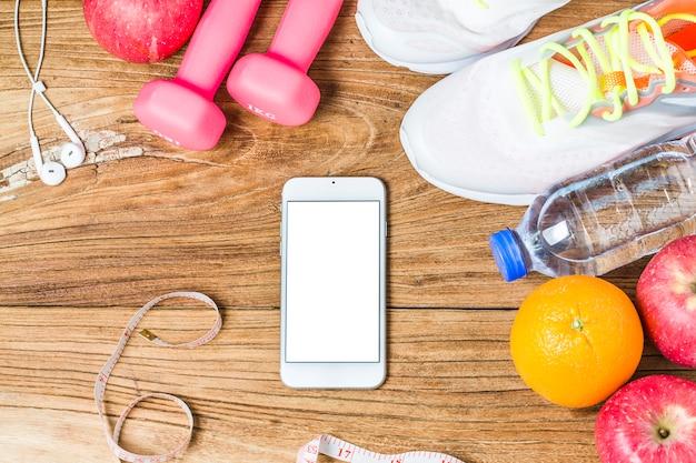 Mode de vie physique, sain et actif concept, bouteille d'eau, haltères, chaussures de sport, smartphone avec casque et pommes sur fond de bois. espace de copie pour le texte. vue de dessus