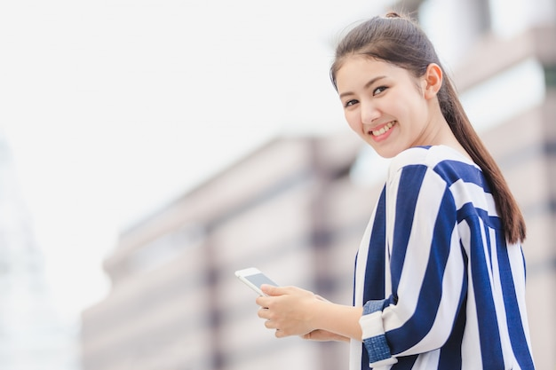 Mode de vie en plein air jeune femme d'affaires à la recherche sur smartphone. concept commercial