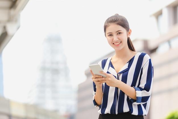 Mode de vie en plein air jeune femme à la recherche sur smartphone.