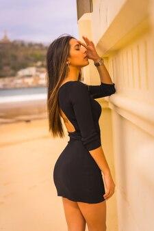 Mode de vie, portrait d'une jeune brune caucasienne de dos dans une courte robe noire, vacances d'été, regardant la caméra avec un look sexy