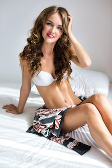 Mode de vie portrait de mode intérieure de femme avec un corps sexy slim fit incroyable, posant sur le lit le matin, vêtu d'une lingerie décontractée simple, détendez-vous et profitez d'une journée ensoleillée.