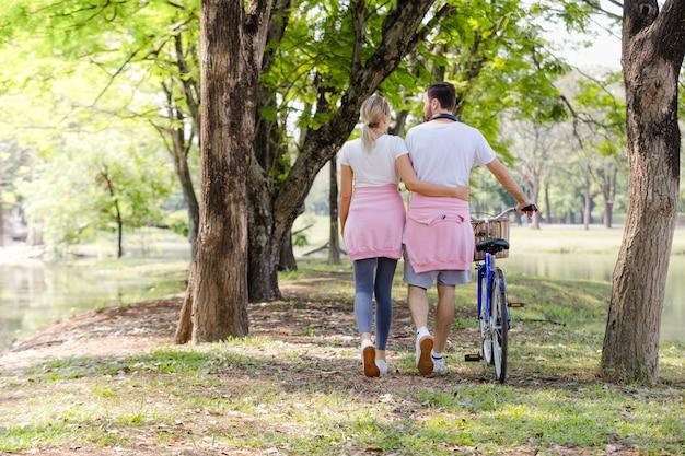 Mode de vie romantique personnes marchant leur vélo le long de parler avec bonheur dans le parc