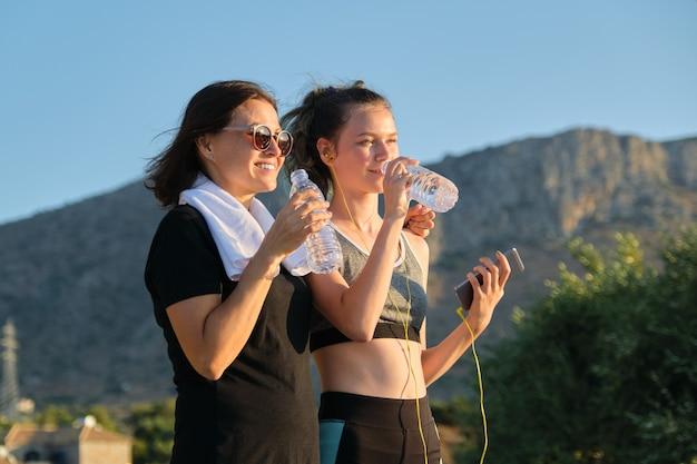 Mode de vie sain et actif, deux femmes adolescentes mère et fille en vêtements de sport parlant et buvant de l'eau après l'entraînement, fond de montagne, coucher de soleil