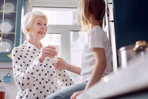 Mode de vie sain. cheerful senior woman donnant un verre de lait à sa petite fille et échangeant des sourires affectueux avec elle tandis que la jeune fille acceptant le verre avec gratitude