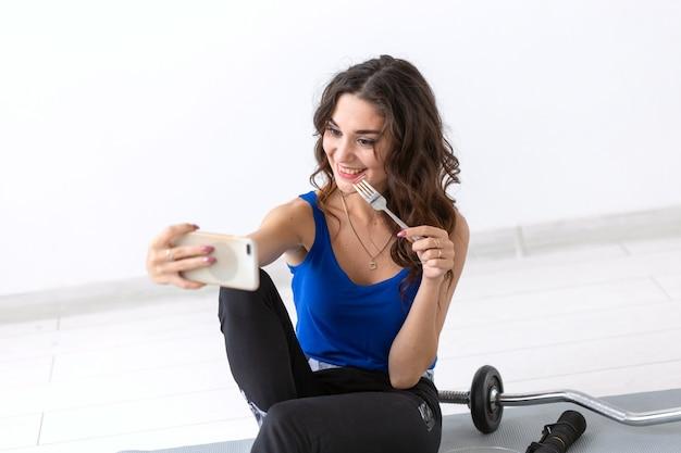 Mode de vie sain, concept de personnes - jeune femme mangeant une salade après le sport et faisant selfie