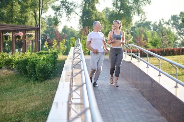 Mode de vie sain. un couple qui court dans le parc le matin