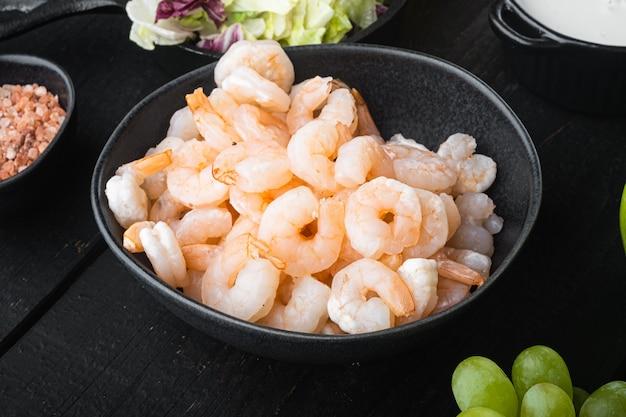 Mode de vie sain - cuisson de salade fraîche de crevettes, salade verte, ensemble d'olives, avec sauce pomme et raisin, sur table en bois noir