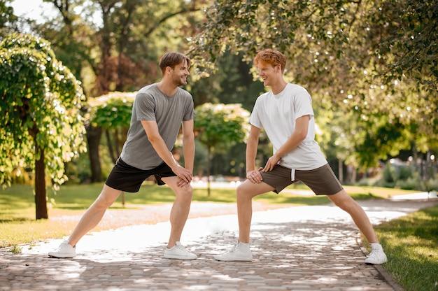 Mode de vie sain. deux amis souriants en short et tshirt debout face à face faisant des exercices d'étirement dans la nature le matin d'été ensoleillé