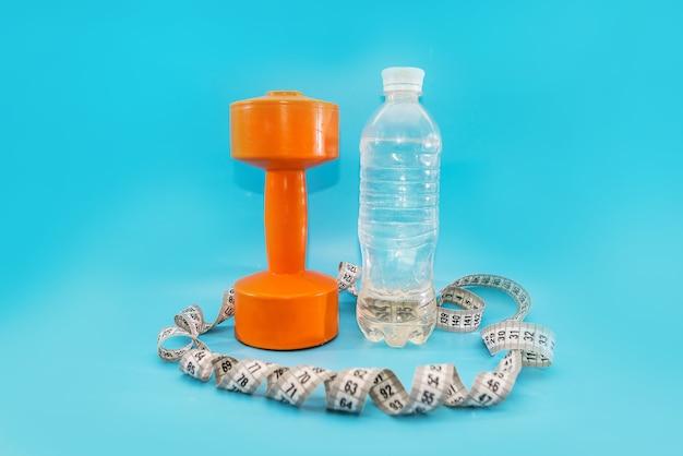 Mode de vie sain, équipements sportifs et sportifs. haltère, ruban à mesurer et bouteille d'eau sur fond bleu.