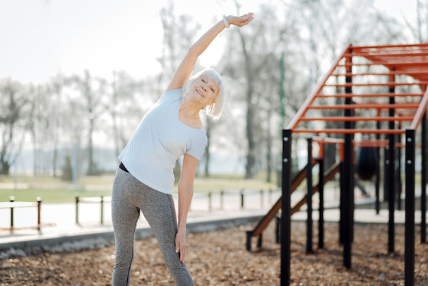Mode de vie sain. femme âgée souriante portant des vêtements de sport et exerçant en plein air