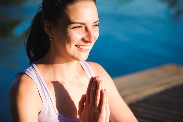 Mode de vie sain femme équilibrée pratiquant la méditation et le yoga énergétique sur le pont le matin la nature.