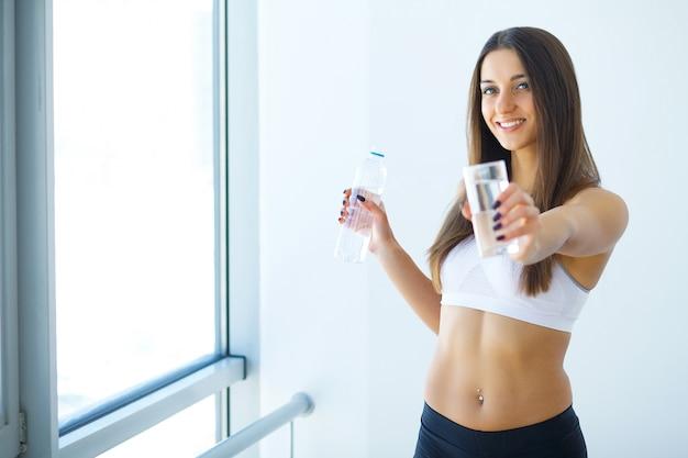 Mode de vie sain. femme heureuse avec un verre d'eau.