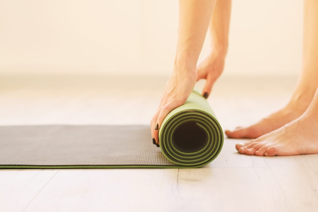 Mode de vie sain - fille utilise un tapis de yoga - rouleau de tapis de sport vue latérale rapprochée