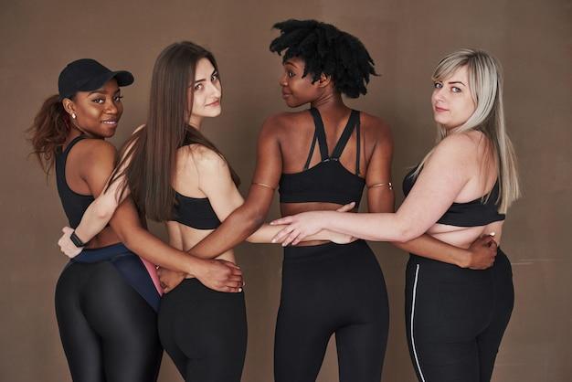 Mode de vie sain. groupe de femmes multiethniques debout contre l'espace brun