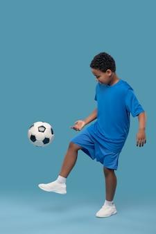 Mode de vie sain. intéressé, un écolier afro-américain impliqué dans des vêtements de sport et des baskets jouant au football sur fond bleu