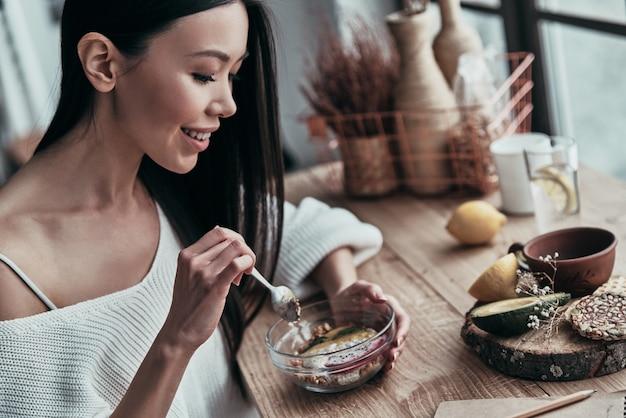 Mode de vie sain. jeune femme attirante mangeant le petit déjeuner sain et souriant