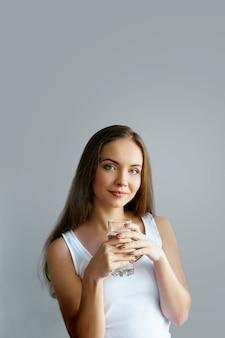 Mode de vie sain jeune femme buvant dans un verre d'eau fraîche
