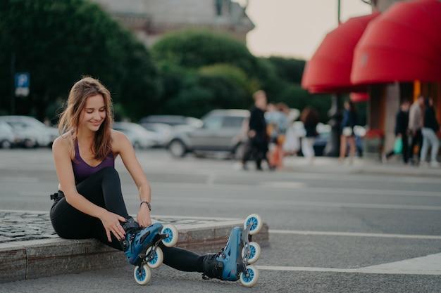 Mode de vie sportif et passe-temps. heureuse femme européenne aux cheveux noirs met des patins à roues alignées pour faire du patin à roues alignées