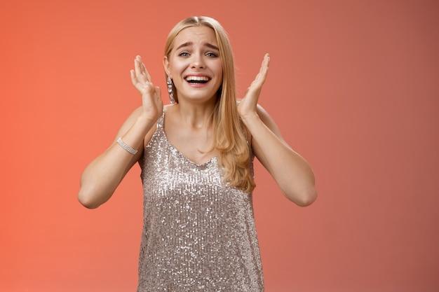Mode de vie. surpris paniqué, fan femme blonde excitée voir la star de célébrité préférée crier étonné regard heureux émotive veux pleurer bonheur en agitant les paumes près de la tête fond rouge ravi.