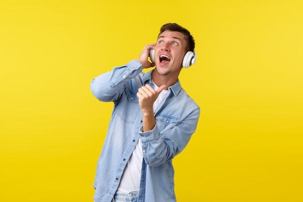 Mode de vie, vacances d'été, concept technologique. beau dj masculin insouciant, mec profitant d'un son impressionnant de musique, montrant le pouce levé dans le coin supérieur gauche, portant des écouteurs sans fil, fond jaune.