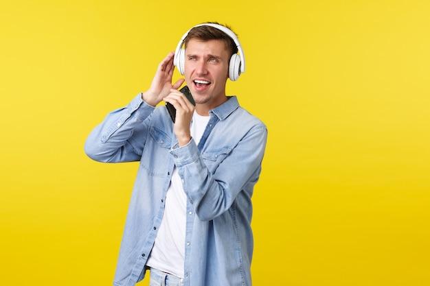Mode de vie, vacances d'été, concept technologique. heureux beau mec blond en tenue décontractée, jouant à l'application de karaoké, chantant une chanson sur un téléphone portable et portant des écouteurs, fond jaune.