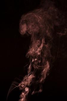 Modèle abstrait fabriqué à partir de fumée s'élevant sur le fond noir