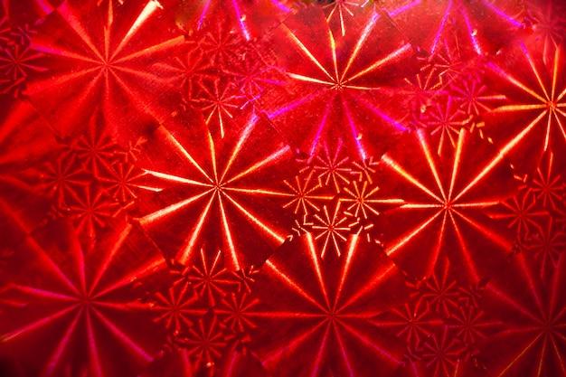 Modèle abstrait avec des rayons sur papier holographique rouge.