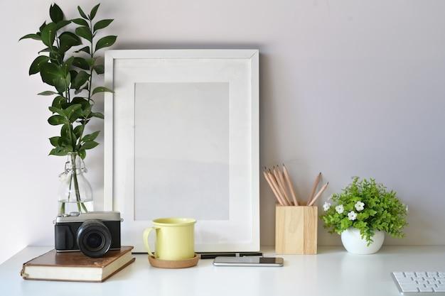 Modèle d'affiche maquette avec appareil photo vintage, fournitures sur l'espace de travail de bureau blanc