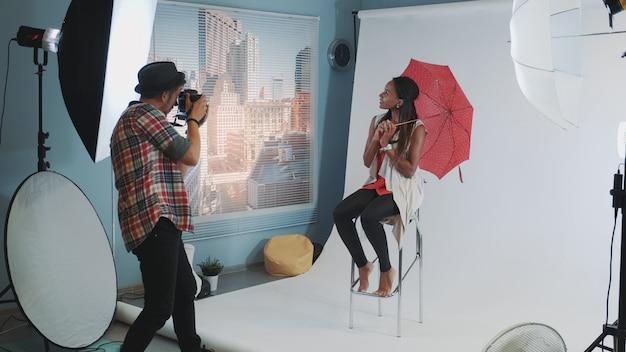 Modèle africain élégant posant avec un parapluie rouge sur une chaise haute de bar pour une séance photo de magazine de mode