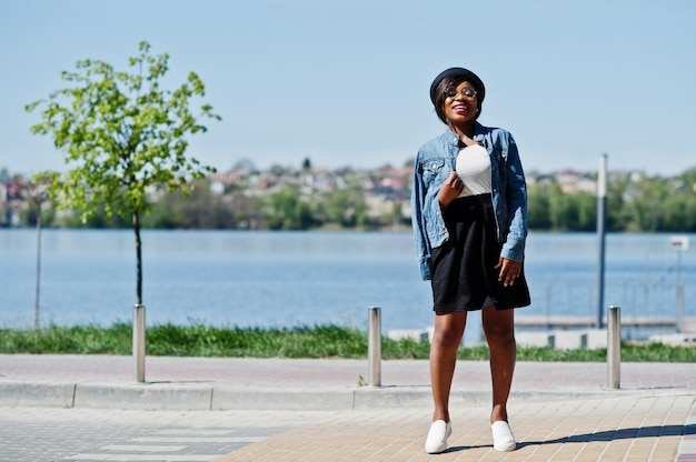 Modèle afro-américain élégant en chapeau de lunettes, veste en jean et jupe noire posée en plein air.