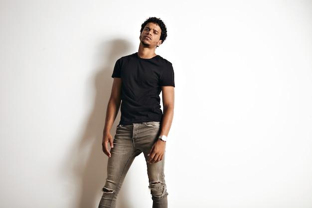 Modèle afro-américain sensuel sexy à la recherche sombre dans un t-shirt noir blanc et un jean skinny sur un mur blanc