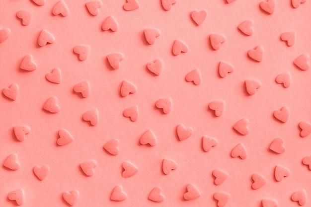 Modèle d'amour romantique. coeurs de confiserie rose pépite sur rose, fond, texture corail tonifié