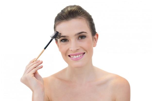 Modèle amusé aux cheveux bruns naturels à l'aide d'une brosse à sourcils